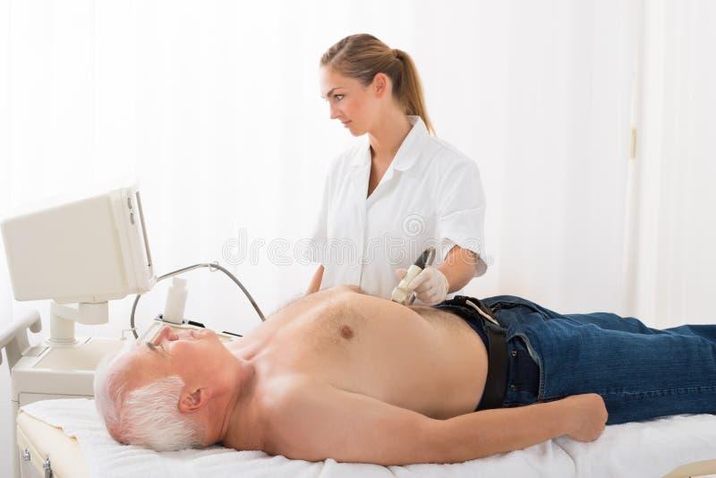 男性患者的Using Ultrasound Scan On医生腹部 图库摄影