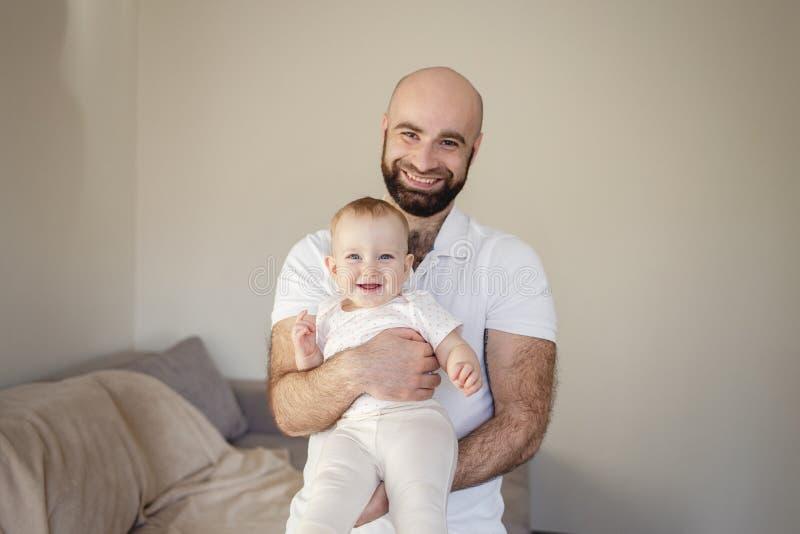 男性成人有胡子的人画象有强的身体的在完善的符合在手上的婴孩 爱的父亲藏品和 免版税图库摄影