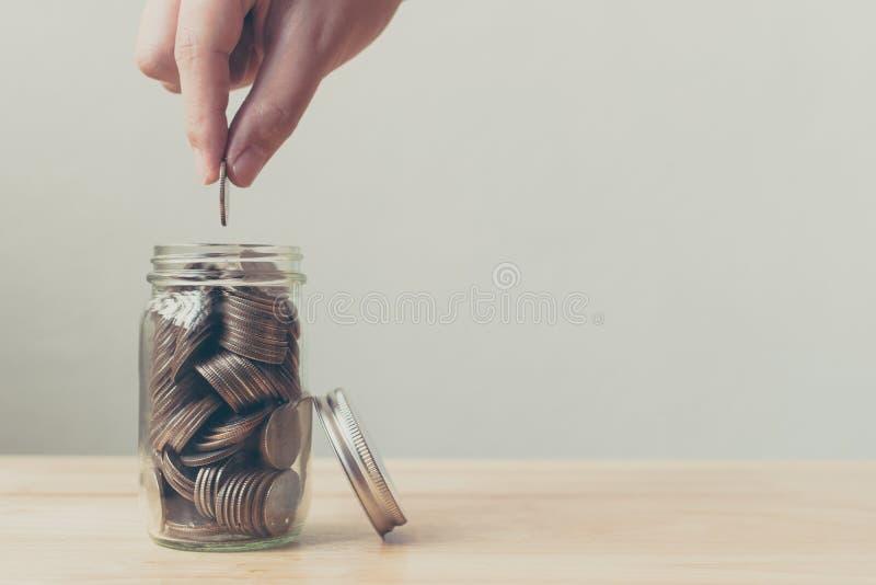 男性或女性投入的硬币的手在瓶子的攒钱的,骗局 免版税图库摄影