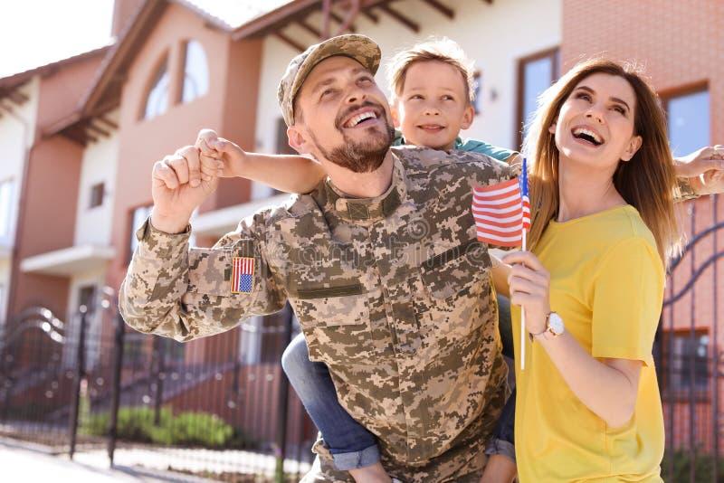 男性战士与他的家庭团聚了,户外 兵役 免版税库存照片