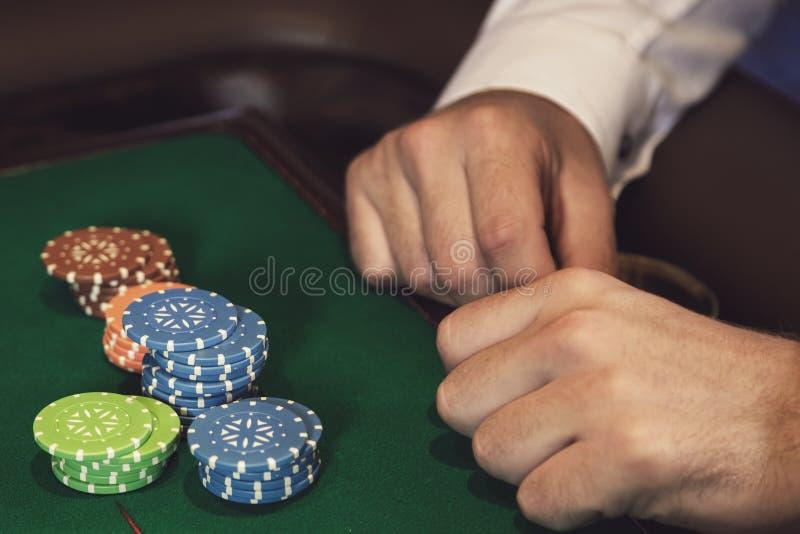男性手和赌博娱乐场芯片 免版税库存图片