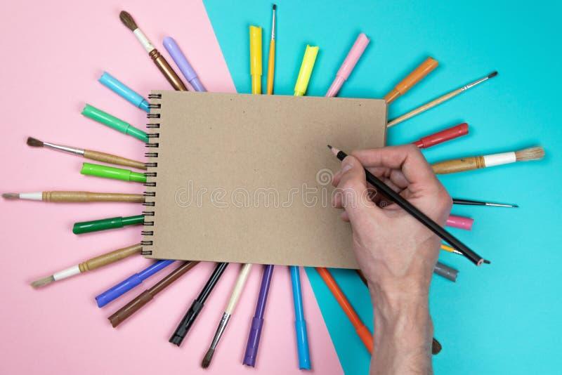 男性手图画、白纸和五颜六色的铅笔 烙记的文具大模型场面,安置的您的设计空白的对象 库存图片