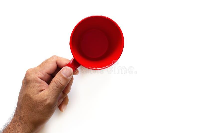男性手在白色背景拿着一个红色杯子被隔绝 图库摄影