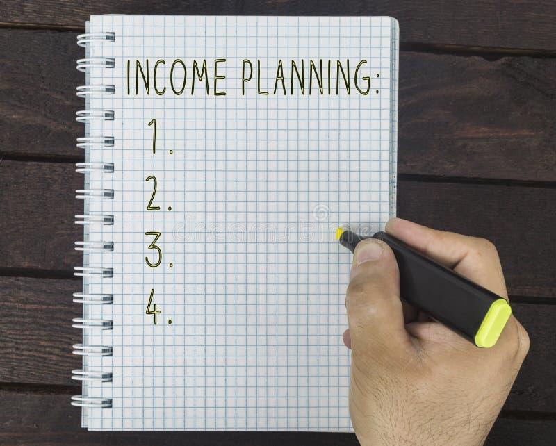 男性手在笔记薄写着收入计划 免版税图库摄影