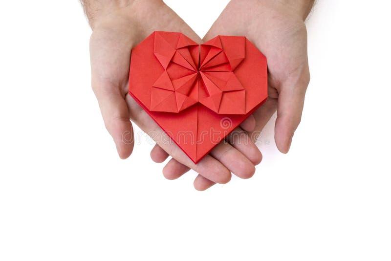 男性手在origami技术拿着红色纸心脏被做 查出 爱,庆祝,关心,健康,生活的概念 库存照片