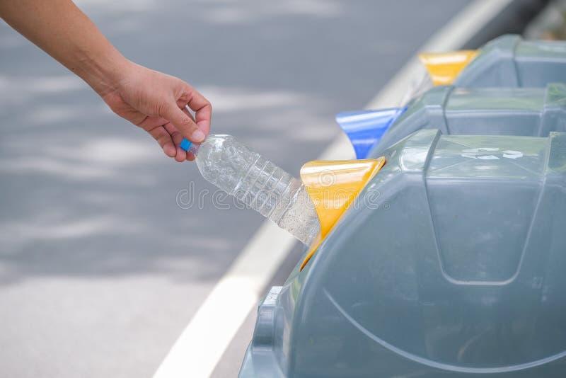 男性手投入了使用的瓶回收站 库存图片