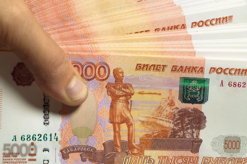 男性手拿着厚实的堆现金金钱 百万俄罗斯卢布 富有、财富、赢利、事务和财务的概念 库存图片