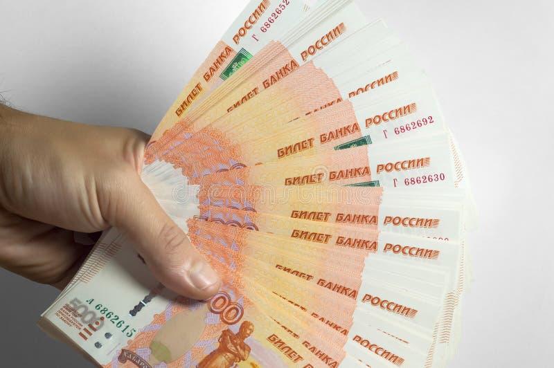 男性手拿着厚实的堆现金金钱 百万俄罗斯卢布 富有、财富、赢利、事务和财务的概念 免版税库存照片