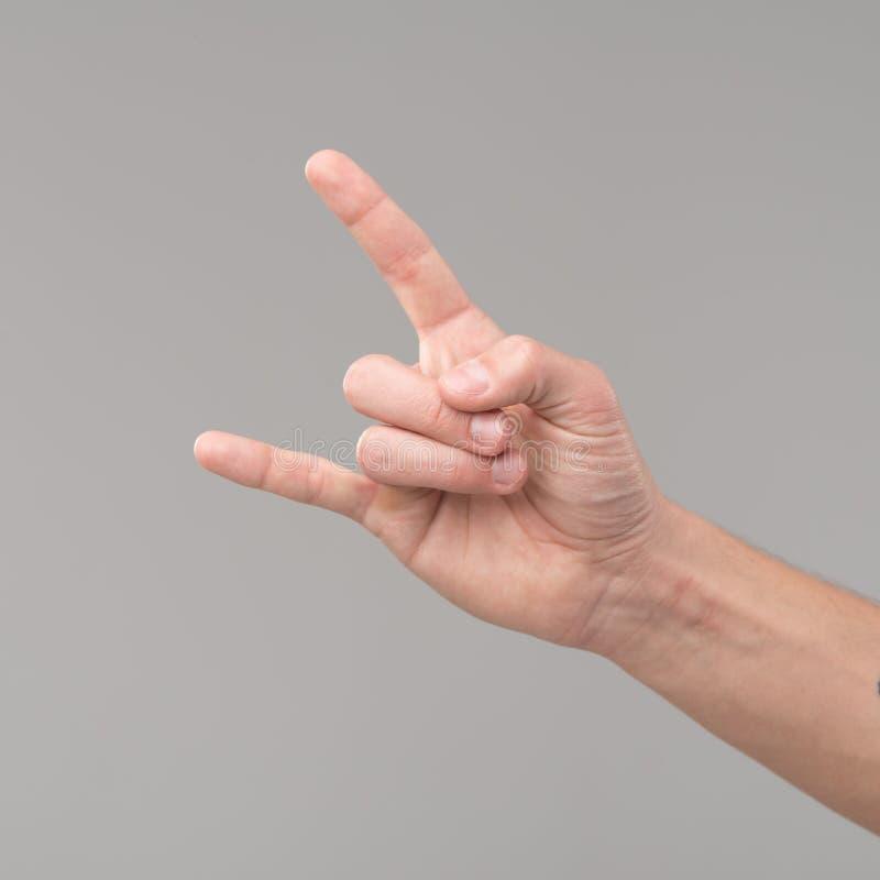 男性手提高了显示一个重金属的岩石标志 免版税库存图片