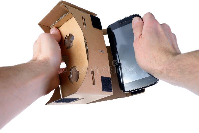 男性手插入手机入VR玻璃纸板 免版税库存图片