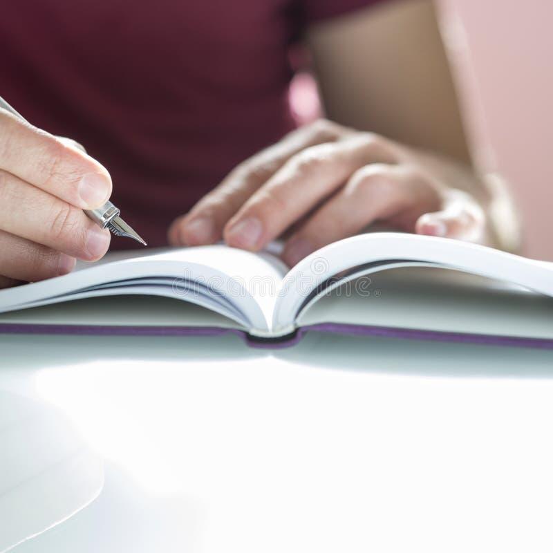 男性手文字的特写镜头在笔记薄的与银色笔 免版税库存照片