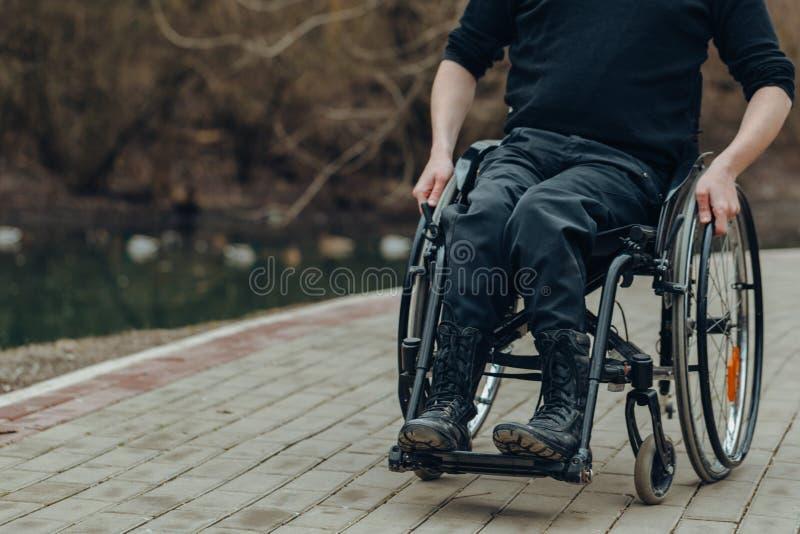 男性手特写镜头在轮椅轮子的在步行期间的在公园 免版税库存照片