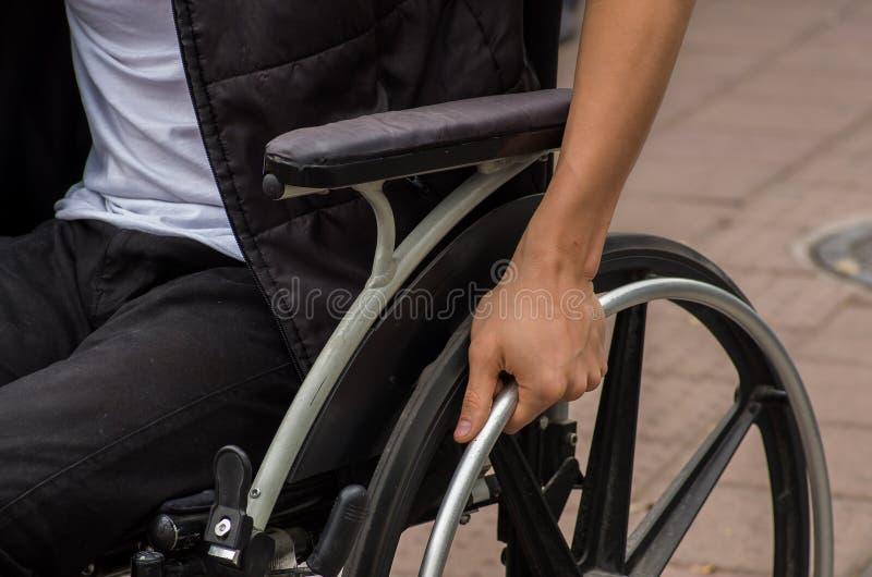 男性手特写镜头在轮椅轮子的在步行期间的在公园 库存图片