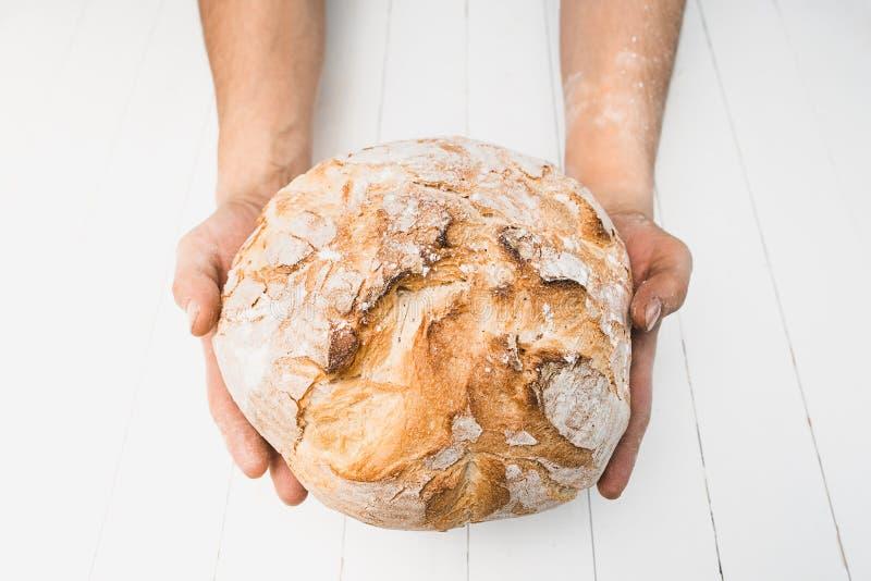 男性手特写镜头在黑背景的一张老土气桌上把新鲜面包放与您的文本的拷贝空间 库存照片