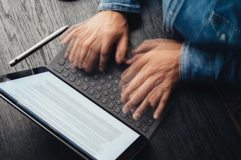 男性手特写镜头视图斋戒键入在电子片剂键盘船坞驻地 关于设备屏幕的企业信息 免版税库存照片