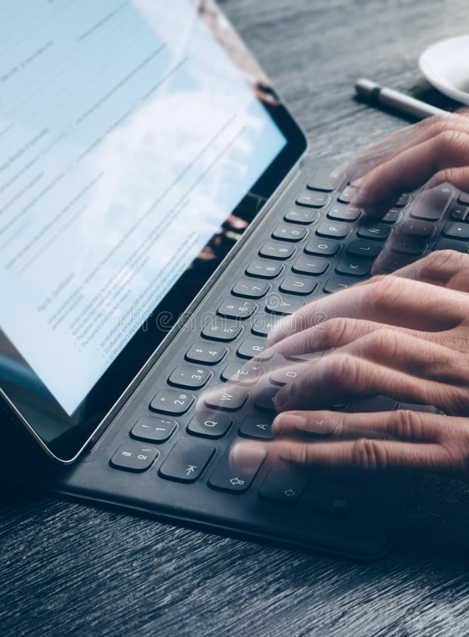 男性手特写镜头视图斋戒键入在电子片剂键盘船坞驻地 关于设备屏幕的文本信息 库存照片