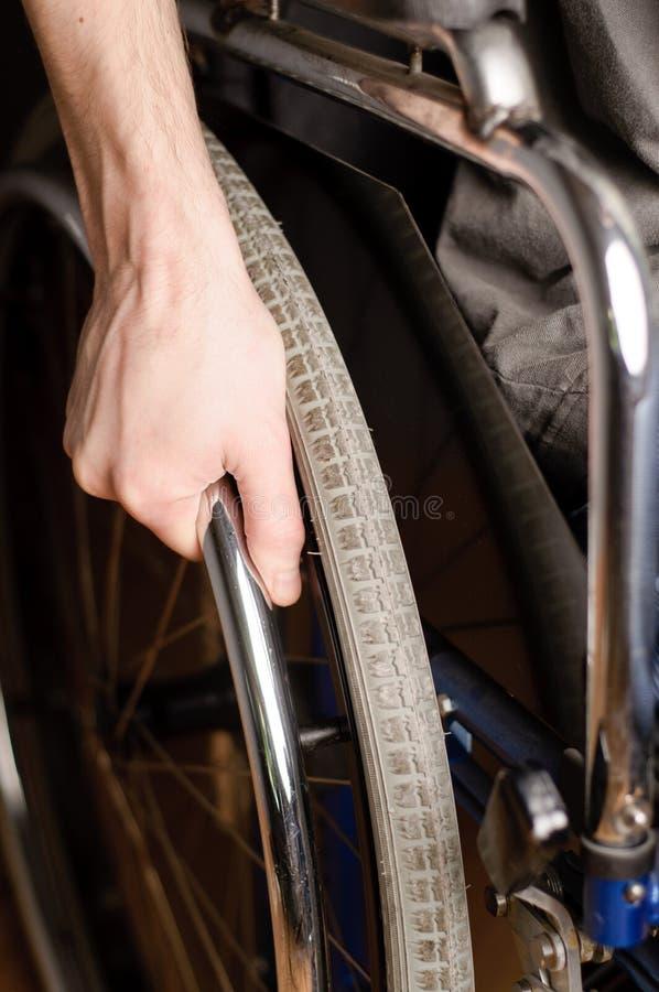 男性手特写镜头在轮椅轮子的  免版税库存图片