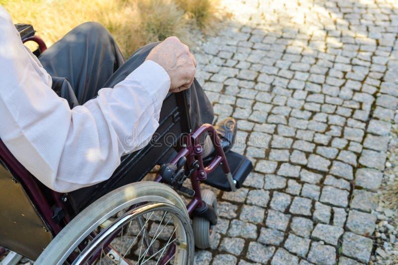 男性手特写镜头在轮椅轮子的 库存照片