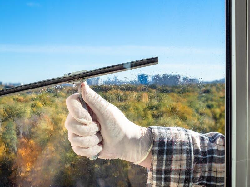 男性手由橡皮刮板清洗家庭玻璃窗 库存照片