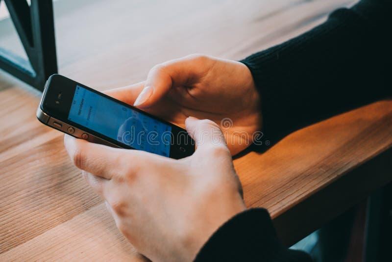 男性手的特写镜头图象使用智能手机的在城市购物街道,搜寻或者社会网络概念上的晚上 免版税库存图片