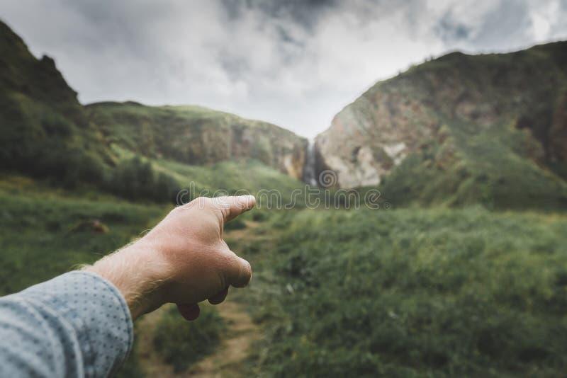 男性手表明移动方向,观点被射击 旅行冒险旅途概念 免版税图库摄影