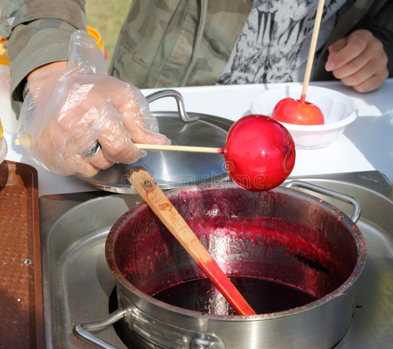 男性手转动在棍子的红色甜苹果在糖浆室外 库存照片