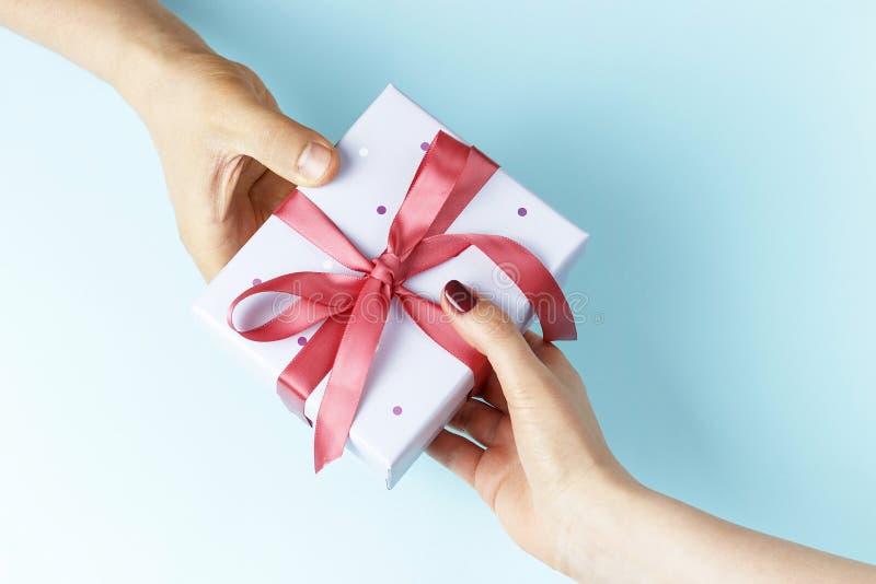 男性手通过礼物盒到女性手,蓝色背景 免版税图库摄影