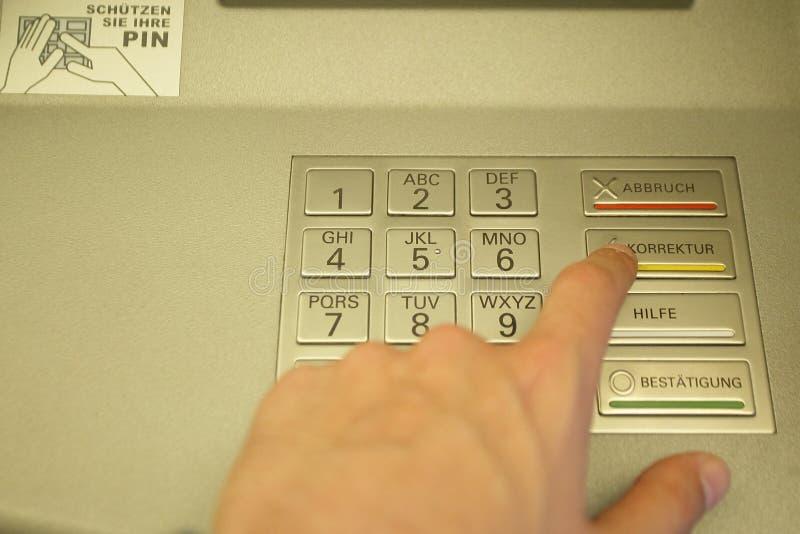 男性手键入代码在现金分送器 现款支付、财务交易和经济概念 免版税库存图片