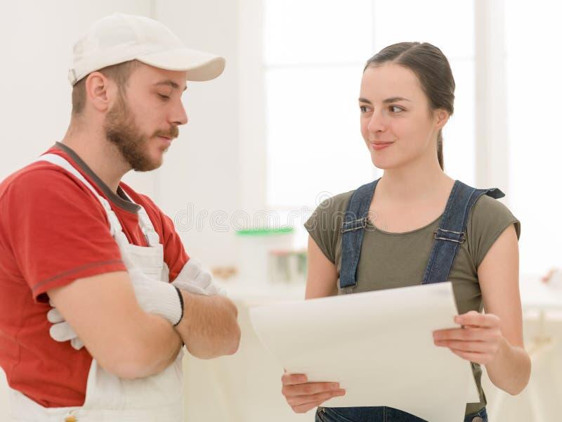 男性承包商谈论计划与妇女在屋子里 免版税库存照片