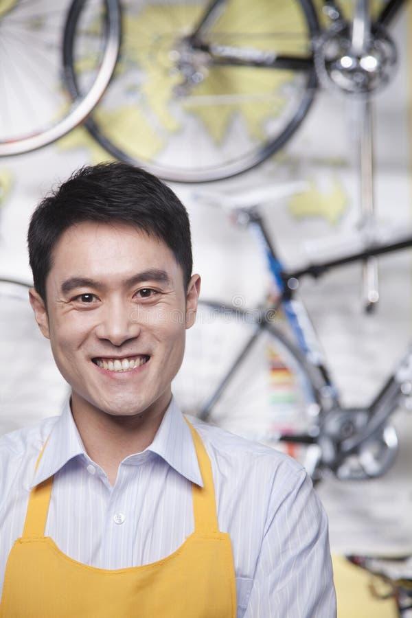 年轻男性技工画象在自行车商店,北京 库存照片