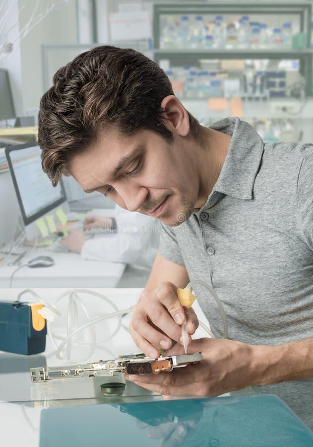 年轻男性技术在研究所运作  库存照片