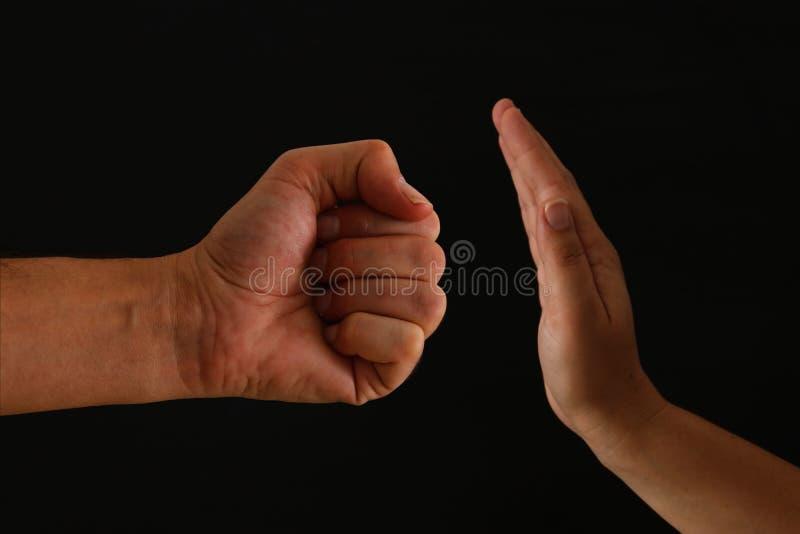 男性拳头的图象和女性手陈列停止 反对妇女的家庭暴力概念 库存照片