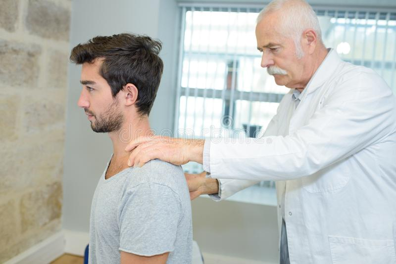 男性按摩医生在康复中心的做脖子调整 免版税库存照片