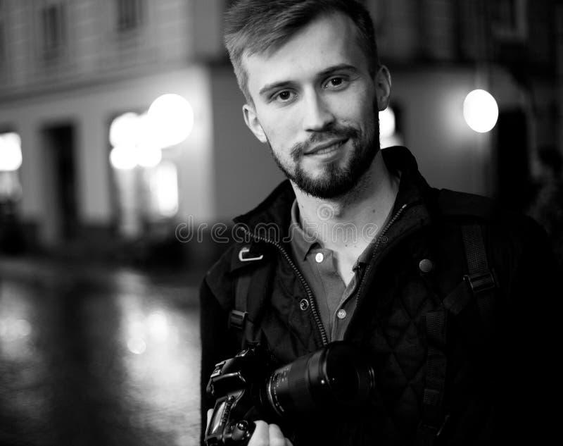 年轻男性摄影师在城市街道上站立在晚上 免版税库存照片