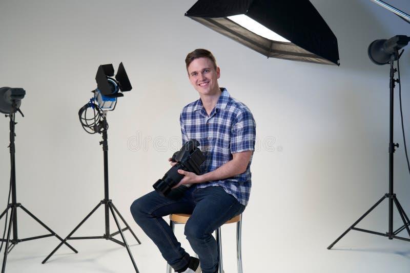 男性摄影师画象在照片写真的演播室与照相机和照明设备 图库摄影