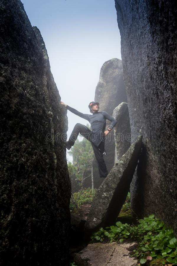 男性攀岩运动员 攀岩运动员在海洋银行的黑岩石墙壁上上升在冰岛, Kirkjufjara海滩 人做 库存图片