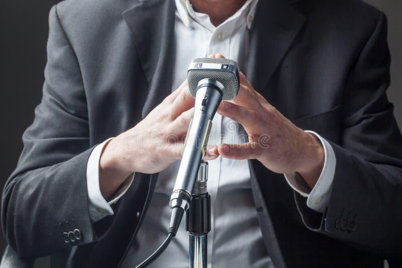 男性政客谈话在有焦点的一个话筒在他的手上 免版税库存照片