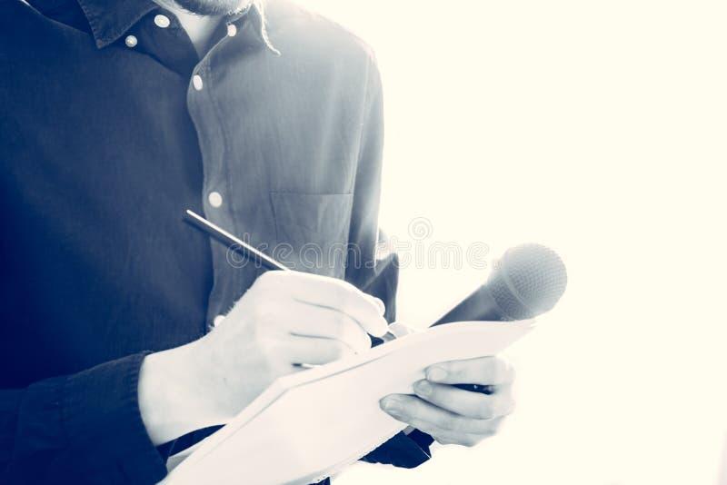 男性新闻工作者在新闻发布会,拿着话筒和采取笔记 库存照片