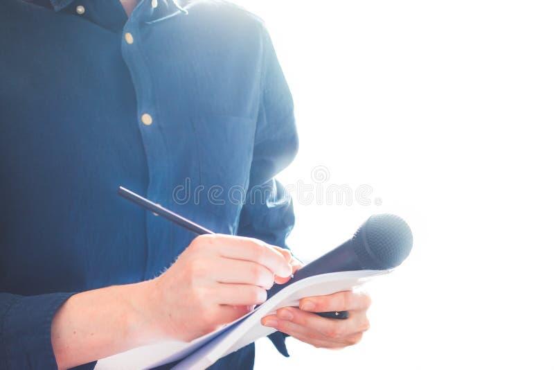男性新闻工作者在新闻发布会,拿着话筒和采取笔记 免版税库存图片