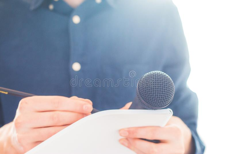 男性新闻工作者在新闻发布会,拿着话筒和采取笔记 库存图片