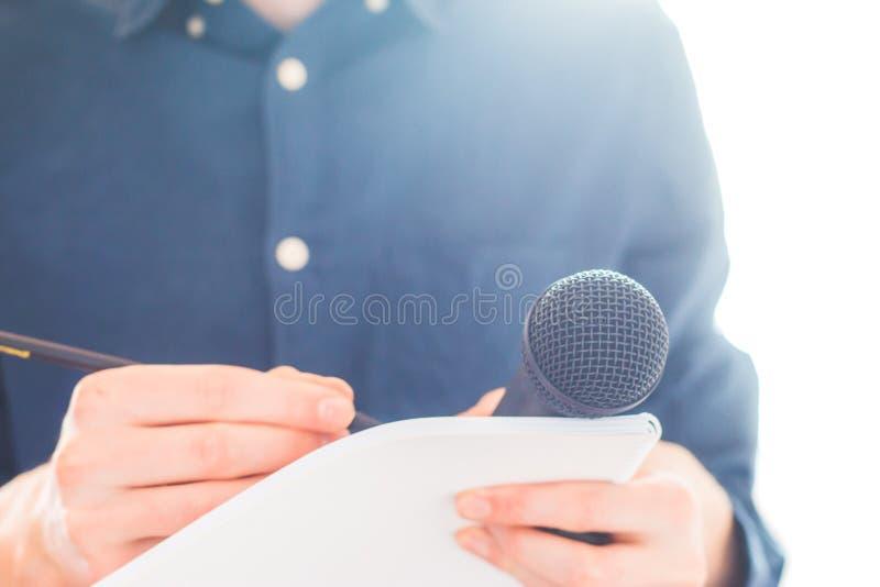 男性新闻工作者在新闻发布会,拿着话筒和采取笔记 免版税库存照片