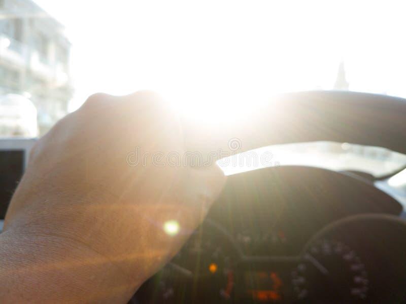 男性方向盘的手,在光 免版税库存图片