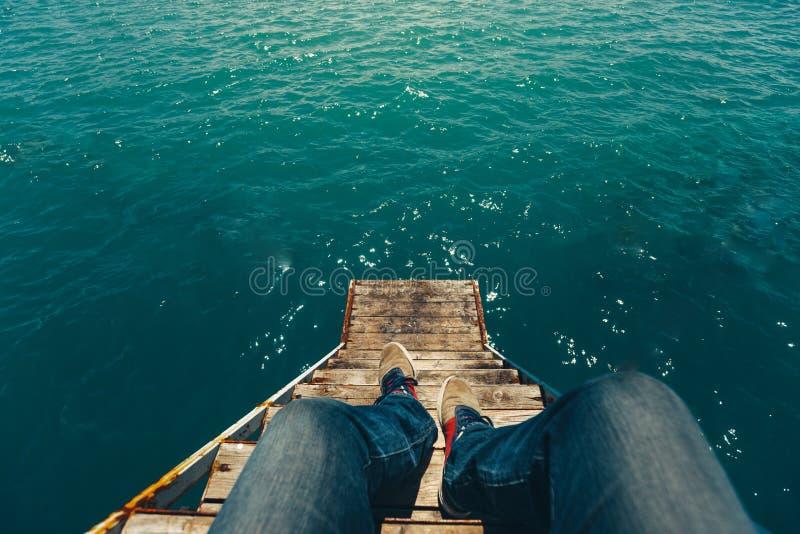 男性旅客坐码头有夏天海视图 旅行Lifes 免版税库存照片
