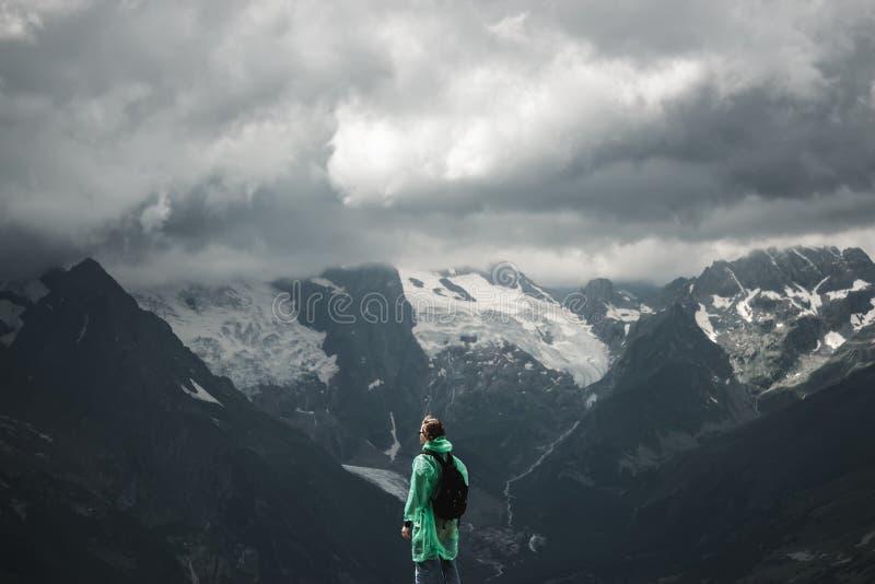 男性旅行家和风雨如磐夏天的山 免版税库存图片