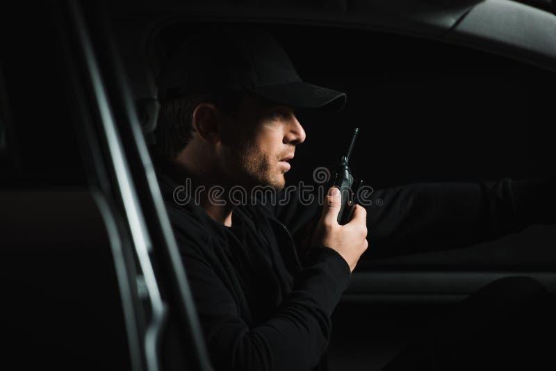 男性无固定职业的摄影师侧视图做监视和使用有声电影walkie的盖帽的 免版税库存照片