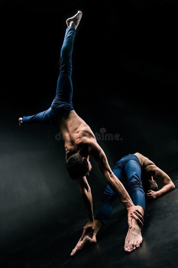 男性杂技二重奏进行在黑暗的背景的一次复杂的平衡操作 库存图片