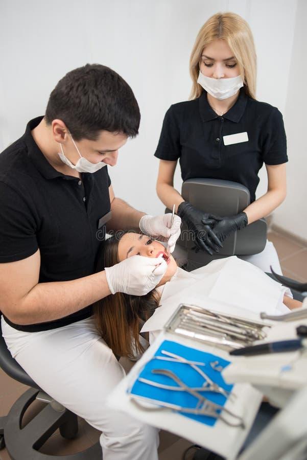 男性检查耐心牙的牙医和女性助理与牙齿工具在牙齿办公室 医学,牙科 免版税图库摄影