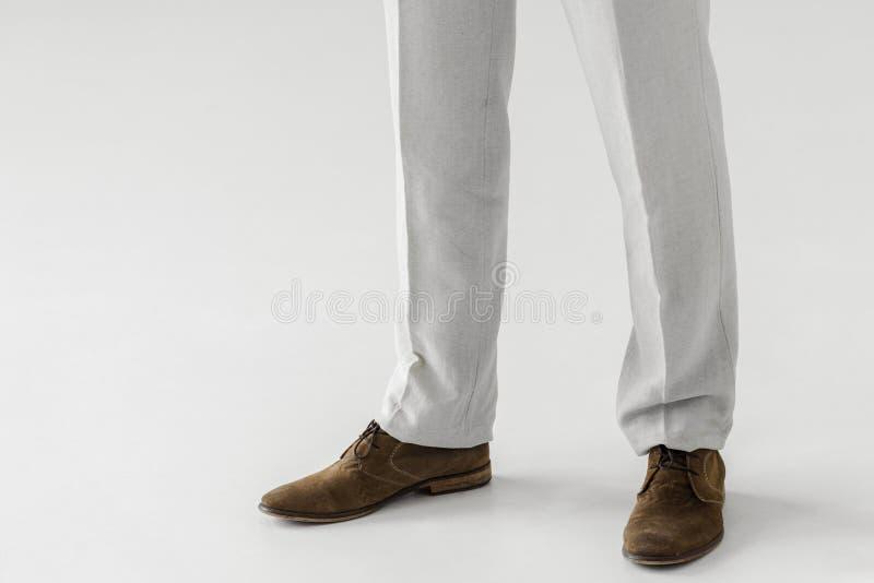 男性模型的播种的图象在亚麻制长裤和绒面革鞋子的 库存图片