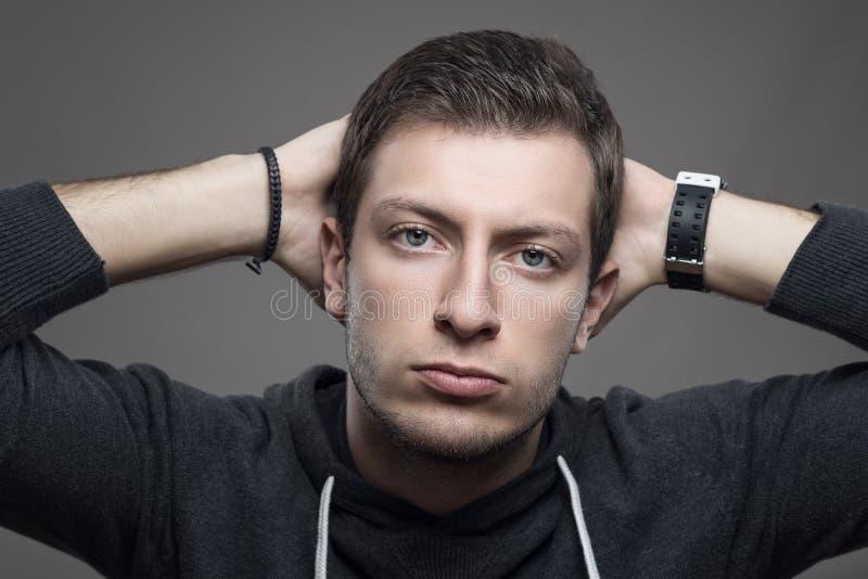 年轻男性模型画象用在看照相机的头后的手 免版税库存图片