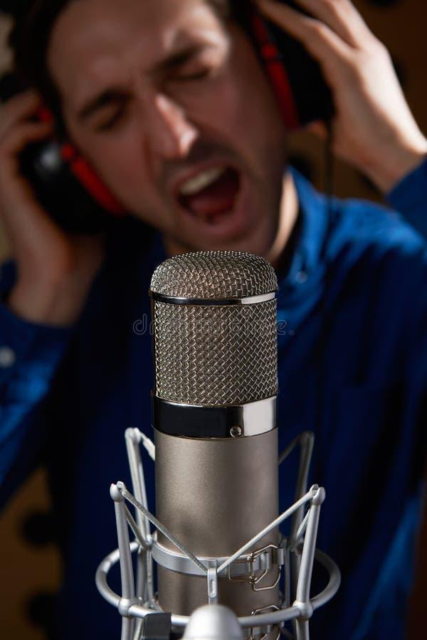 男性歌唱者在录音室 免版税库存图片